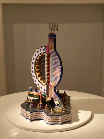 U.N. (1995): A sculpture combining elements from a gridded, modernist skyscraper with one of scalloped half-circular forms prevalent in Kingelez's work. A hybrid of the kind only Kingelez could conjure.